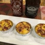 Three barbecue breakfast cupcakes on serving platter with sriracha and barbecue sauce