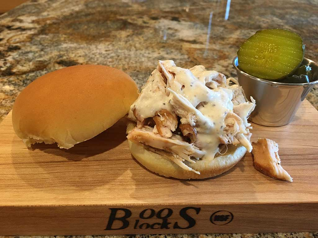 Alabama-style pulled chicken sandwich drizzled with white sauce