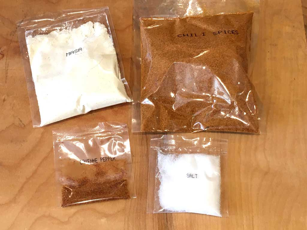 Pre-measure packets of chili spices, cayenne, salt, and masa flour