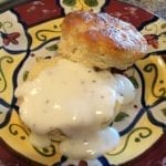 Close-up of a split black pepper biscuit with country gravy