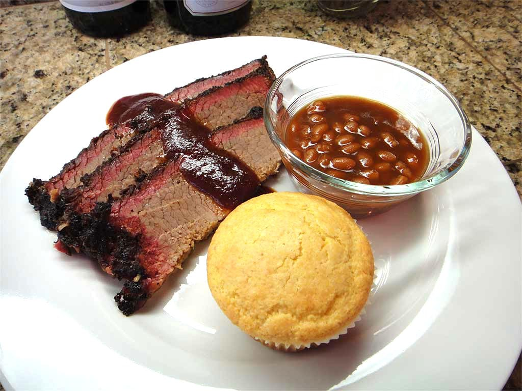 Sliced brisket with sauce, beans & corn muffin