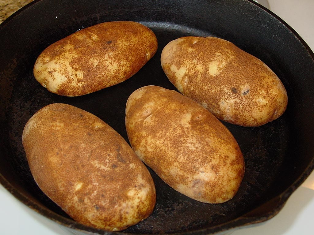 Buttered potatoes face down in iron skillet