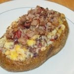 Twice-baked potato topped with butter, cheese, and more brisket