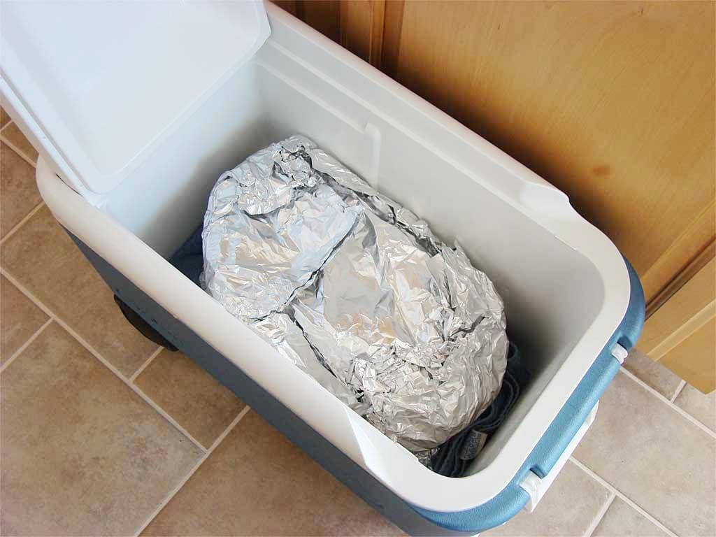 Foiled brisket resting in empty cooler
