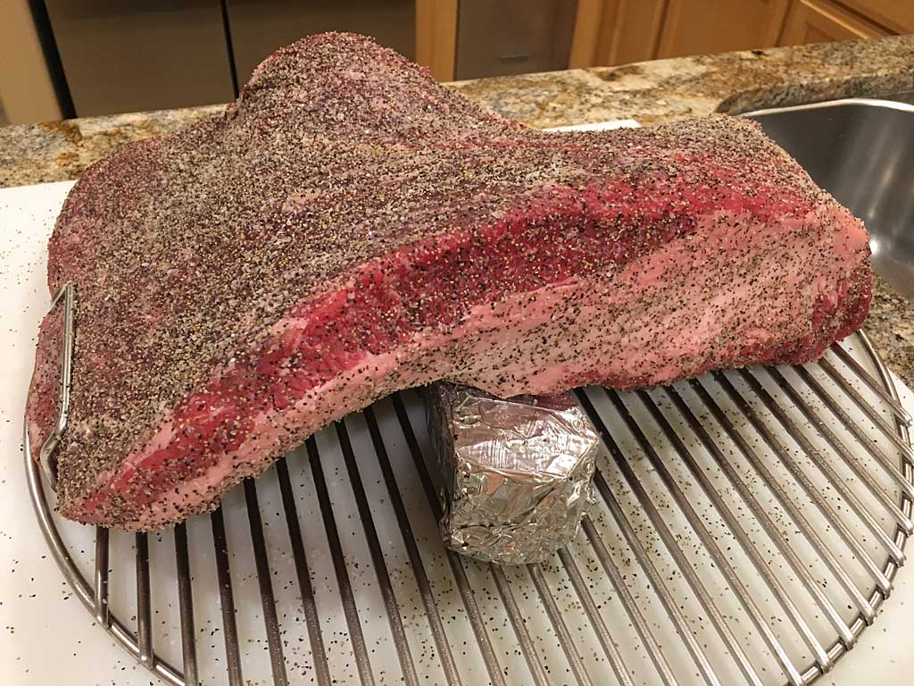Brisket draped over foil-wrapped smoke wood chunk