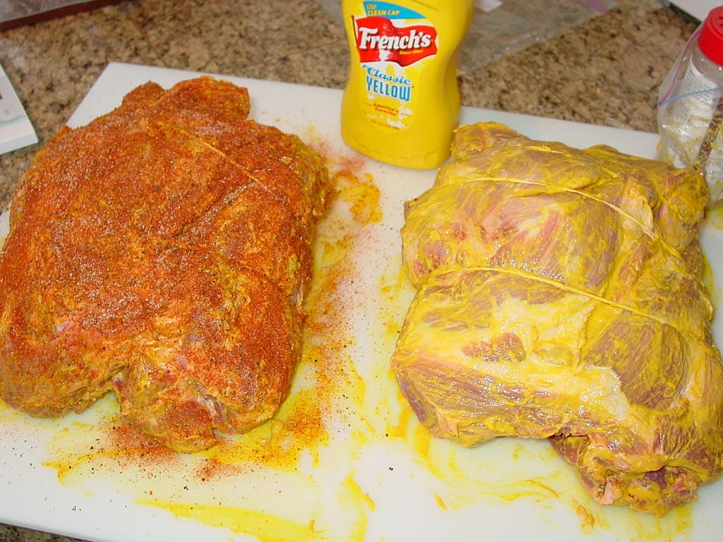 Pork butts slathered with mustard and rub