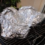 Foiled pork butts go back into the WSM for at least 2 more hours.