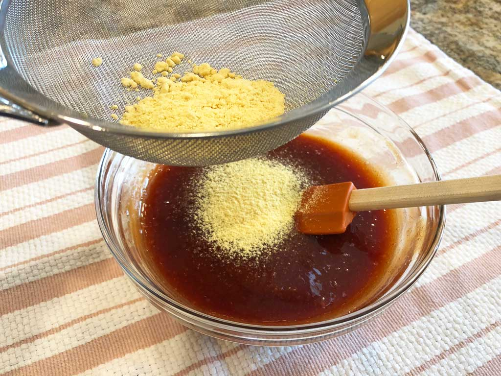Sifting dry mustard into sauce