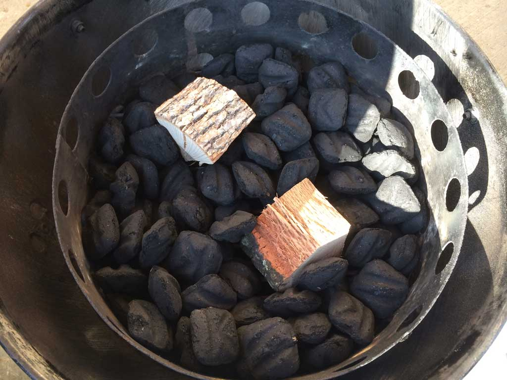 Smoke wood on top of unlit charcoal briquets