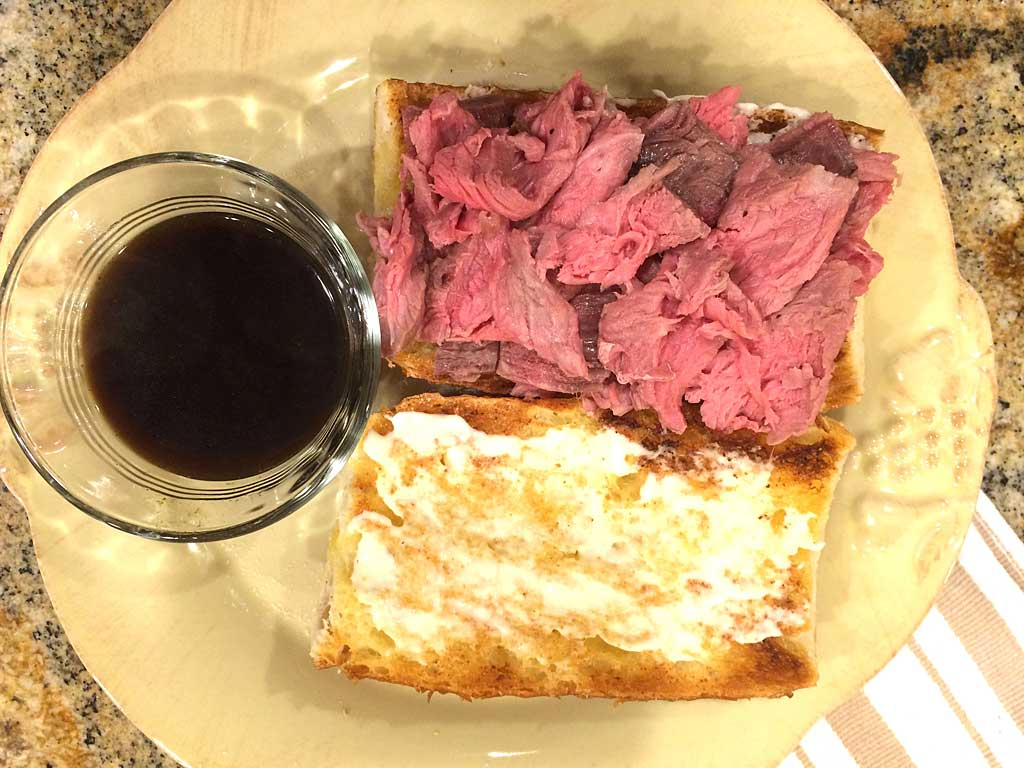 Sliced rib roast on toasted roll with garlic butter, creamy horseradish and au jus