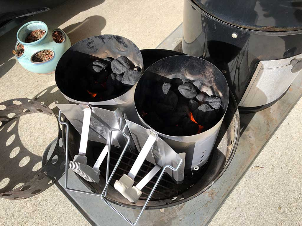 Lighting two Weber chimney starter of charcoal