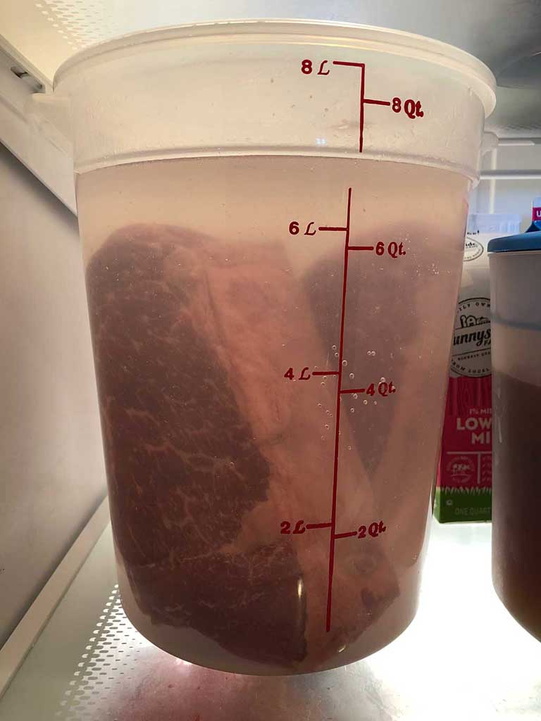 Soaking corned beef in water to reduce saltiness