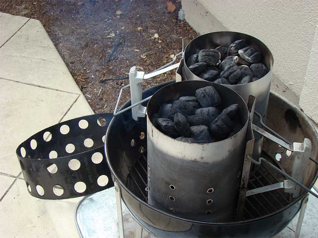 Two Weber chimney starters lighting Kingsford charcoal