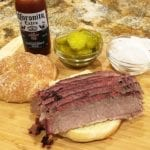 Brisket sandwich with pickles, onions, and sauce on the side