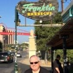 Chris Allingham posing with the Franklin Barbecue sign