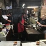Staff cutting meat and filling orders behind the counter