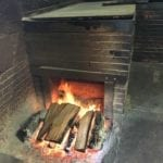Open wood fire drafts into a backroom pit