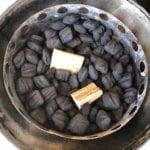 Wood chunks nestled into unlit charcoal