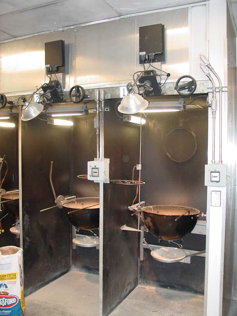 "Test stations in the Weber burn room. A charcoal ring hangs on the back wall. The circular thermocouple array is shown about 12"" above and to the left of the kettle on the right. The gray box outside each station is a timer. The black box above each station is an interface that connects test equipment to a monitoring computer."