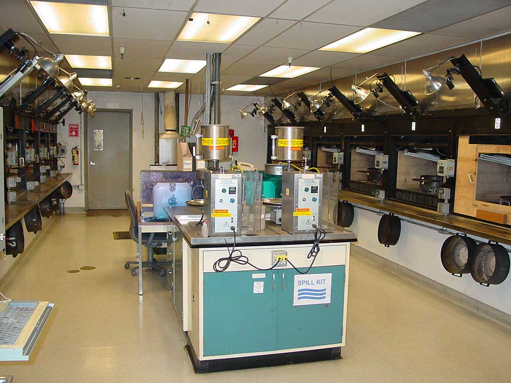 The division lab burn room. The two machines on the table in the foreground apply a measured amount of solvent to each charcoal sample prior to lighting. Charcoal rings are seen hanging below each test station. Not shown in this photo is a special test station that burns charcoal on a scale so weight can be measured throughout the burn test.