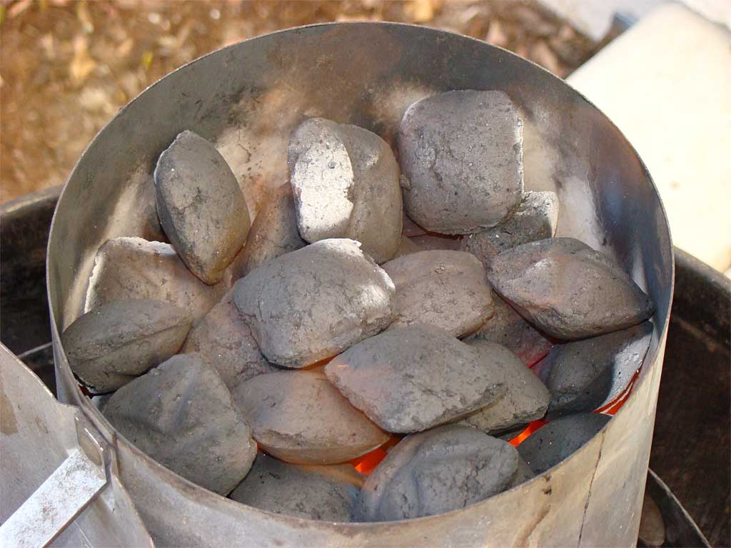 Close-up of lit charcoal in chimney starter