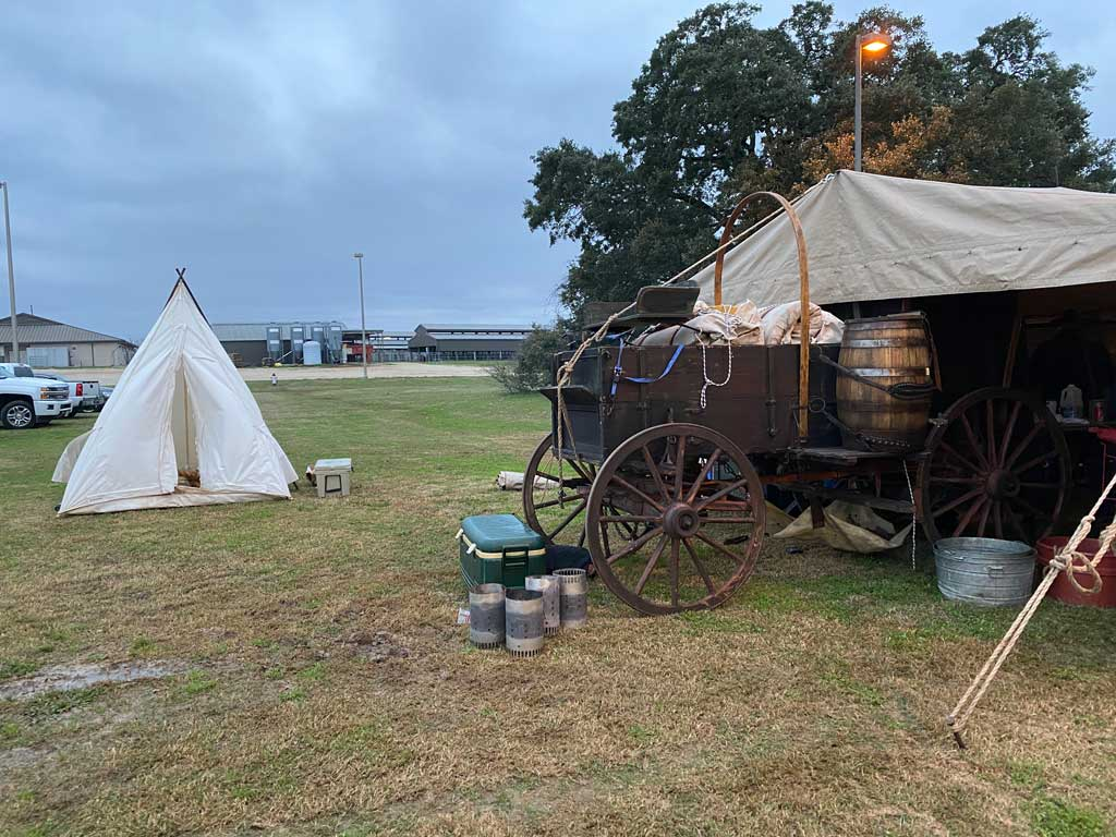 Chuck wagon nosed under a canopy and nearby teepee tent