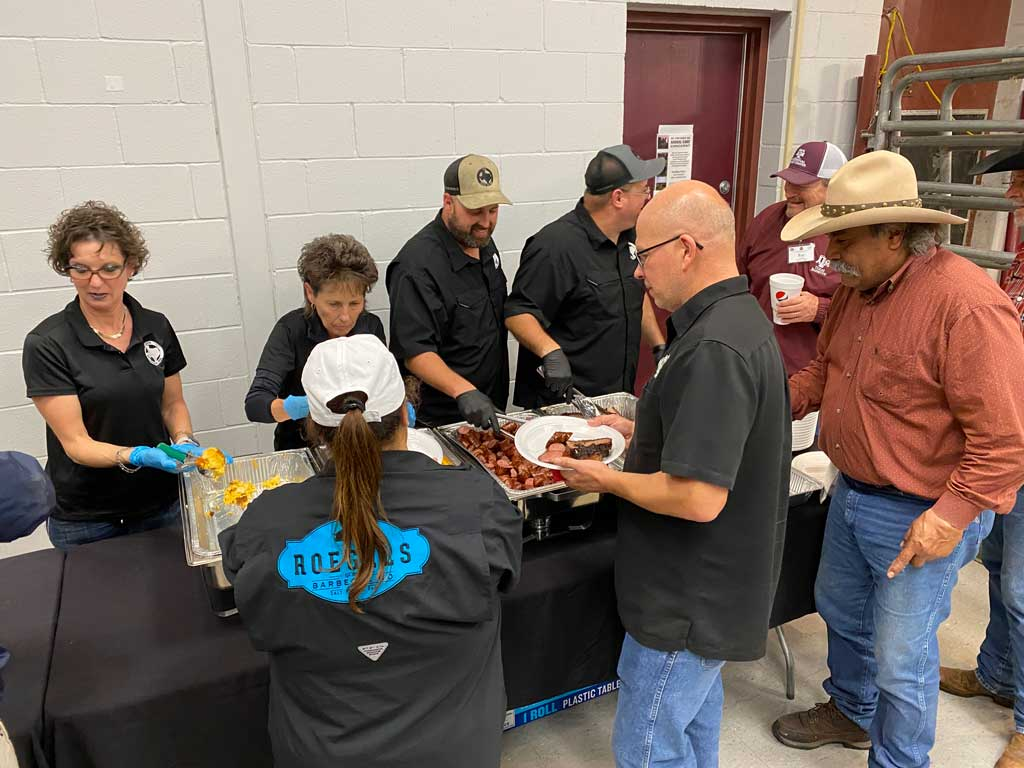 Hungry Camp Brisket students line up for brisket, sausage, sides and dessert