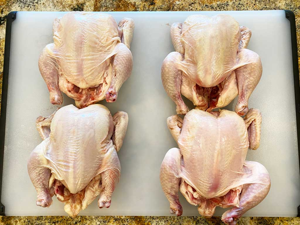 Four unwrapped, patted dry Cornish game hens on cutting board