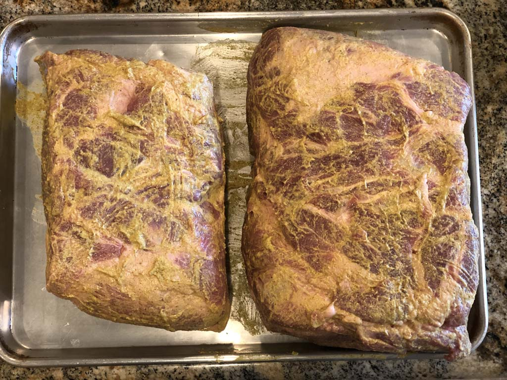 Pork butts slathered with brown mustard