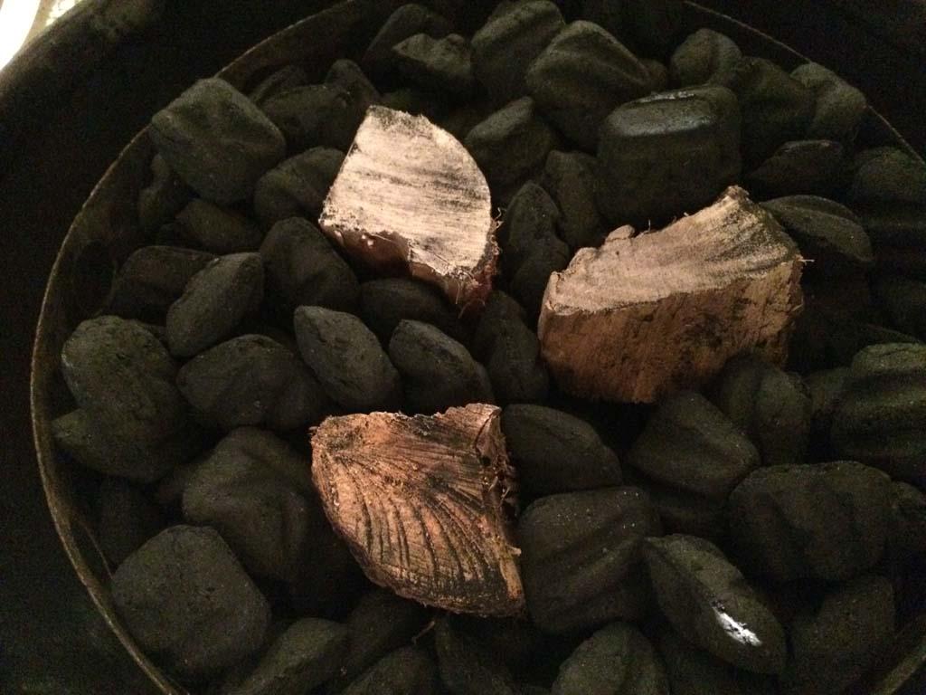 Smoke wood chunks nestled into unlit charcoal